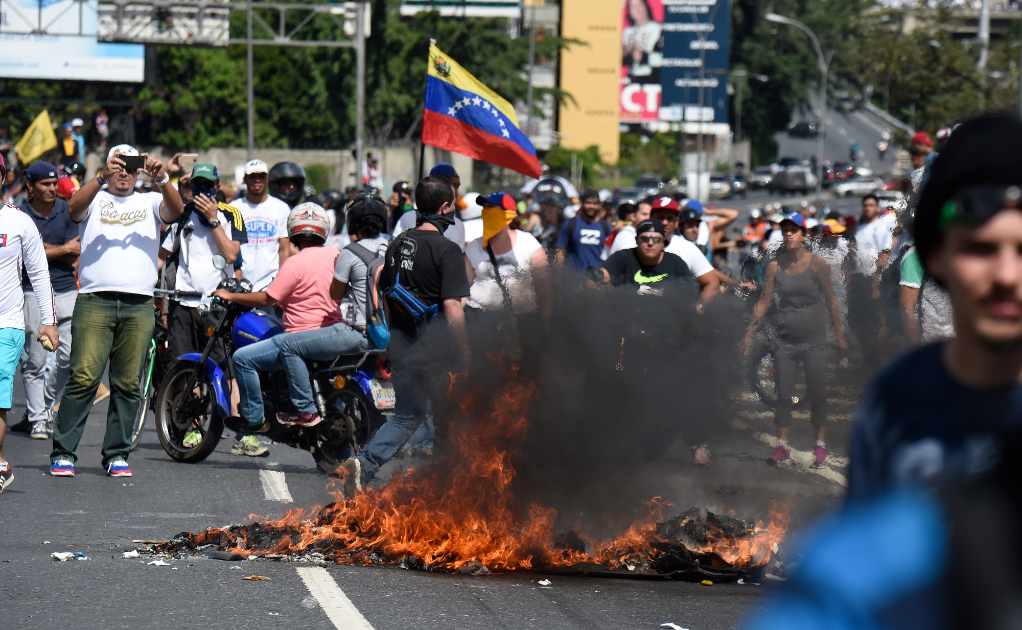 Riot police and opposition activists clash during a march in Caracas, on September 1, 2016. Venezuela's opposition and government head into a crucial test of strength Thursday with massive marches for and against a referendum to recall President Nicolas Maduro that have raised fears of a violent confrontation. / AFP PHOTO / JUAN BARRETO