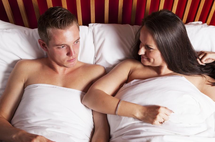 Mujer y hombre joven en la cama