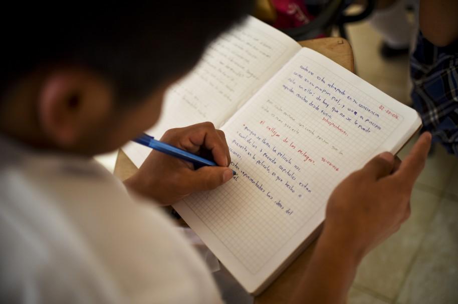 Niño escribe en un cuaderno