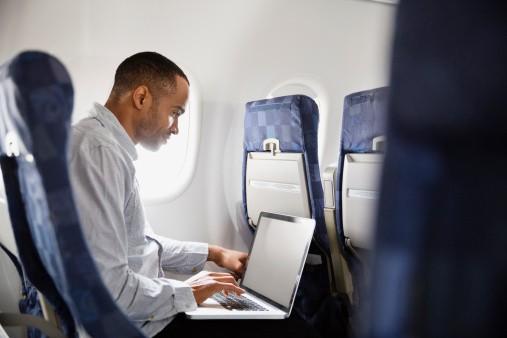 Hombre con portátil en avión