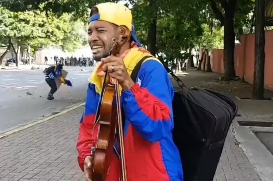 Manifestante con violín destruido