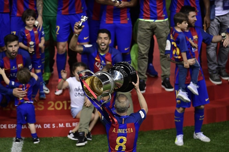 Andres Iniesta holds up the cup