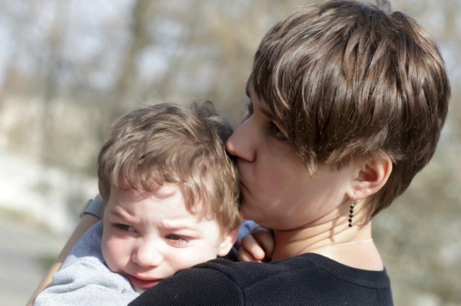 Madre abraza a hijo.