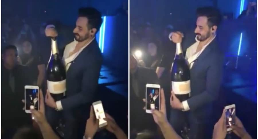 Hombre abre botella de champaña en Ibiza.