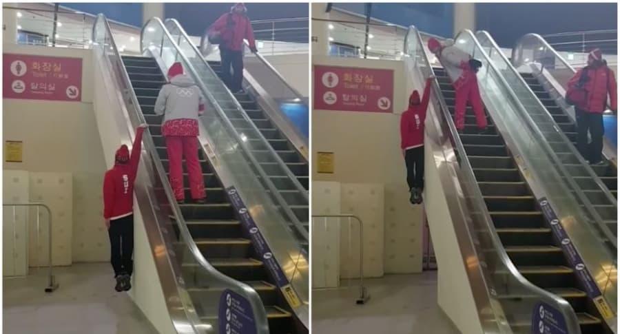 Hombre sube escalera eléctrica colgado.