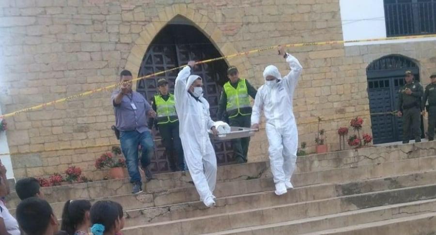 Momento en el que miembros de criminalística levantan el cuerpo del niño del templo