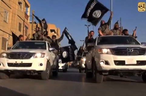 """A screen grab taken from a video released on July 1, 2014, allegedly shows members of the IS (Islamic State) parading on a street in the northern rebel-held Syrian city of Raqa. AFP PHOTO / HO / WELAYAT RAQA === RESTRICTED TO EDITORIAL USE - MANDATORY CREDIT """"AFP PHOTO / HO / WELAYAT RAQA"""" - NO MARKETING NO ADVERTISING CAMPAIGNS - DISTRIBUTED AS A SERVICE TO CLIENTS FROM ALTERNATIVE SOURCES, AFP IS NOT RESPONSIBLE FOR ANY DIGITAL ALTERATIONS TO THE PICTURE'S EDITORIAL CONTENT, DATE AND LOCATION WHICH CANNOT BE INDEPENDENTLY VERIFIED ==="""