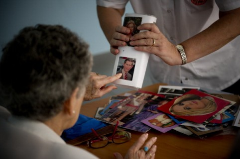 BARCELONA, SPAIN - AUGUST 02:  Social worker Nuria Casulleres shows a portrait of Prince Charles, Prince of Wales to an elderly woman during a memory activity at the Cuidem La Memoria elderly home, which specializes in Alzheimer patients on August 2, 2012 in Barcelona, Spain. Nuria Casulleres, whose only daughter lives at home while attending University, is accustomed to 900 euros monthly for income. With The Catalan Government government cutbacks she is now only receiving 800 euro with rent taking 650 of that income. The Government currently cannot pay the July allocations to old age homes and others social services as a result of liquidity issues. According to reports, Spain's most indebted region, Catalonia, is not be able to pay 400 millions euros in grants. Approximately one hundred thousand social workers will see their salary cut by 40% to 50% while relatives of elderly home residents have had to help pay the salaries and expenses.  (Photo by David Ramos/Getty Images)
