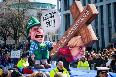 "A carnival float depicting German chancellor Angela Merkel carrying a cross reading ""humane refugee politics"" and Bavarian state premier Horst Seehofer shouting ""crucify her"" is displayed during a street parade on March 13, 2016 in Duesseldorf, western Germany. The street parade was postponed due to a storm warning. / AFP / dpa / Monika Skolimowska / Germany OUT"